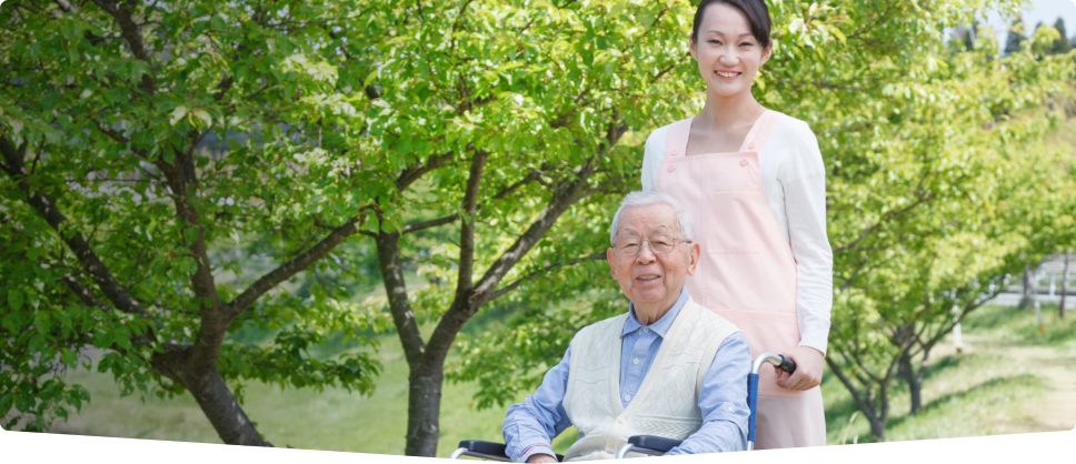 caregiver standing at the back of old man sitting on a wheelchair